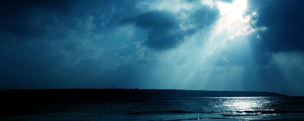 雲の隙間から海に向かって光が差し込んだ写真